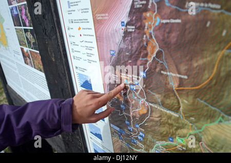 Young woman looking at trail map before hiking in Peñalara, highest mountain peak in the mountain range of Guadarrama, - Stock Photo