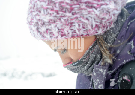 Young woman faces blizzard while hiking in snowy day at Penalara, highest mountain peak in the mountain range of - Stock Photo