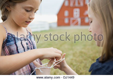 Little girls playing cats cradle outdoors - Stock Photo