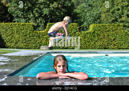 A girl looks at the photographer whilst a boy jumps in behind her - Stock Photo