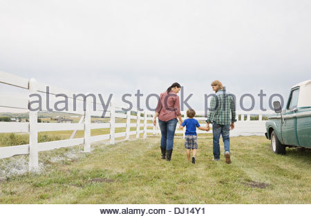 Family of three walking together on farm - Stock Photo