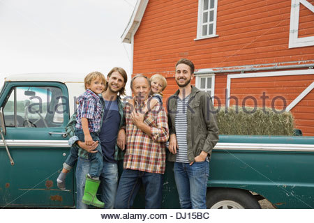 Happy three generation male family standing by pick-up truck - Stock Photo