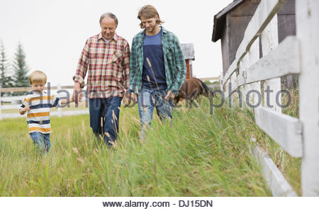 Three generation male family walking together on grassy field - Stock Photo