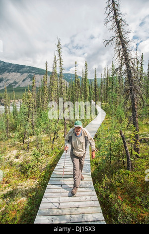 Man Walking Along The Boardwalk Near Virginia Falls In Nahanni National Park Reserve; Northwest Territories, Canada - Stock Photo