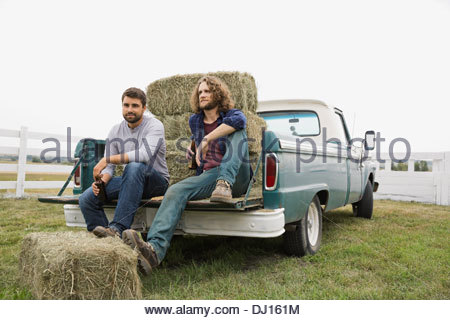 Friends sitting against hay bales in back of pick-up truck - Stock Photo