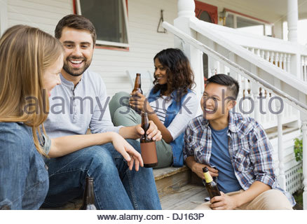 Group of friends enjoying drinks on porch - Stock Photo