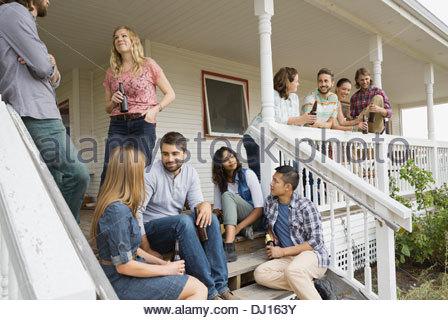 Multiethnic friends enjoying party on porch - Stock Photo