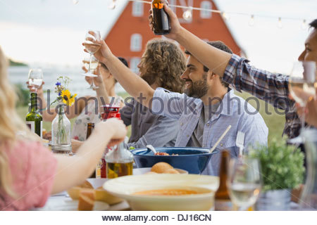 Group of friends toasting drinks at dinner party - Stock Photo