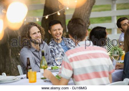 Multiethnic friends enjoying outdoor dinner party - Stock Photo