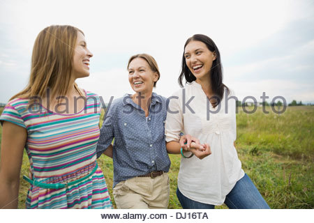 Affectionate female family members walking through field - Stock Photo