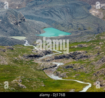 Heart-shaped lake and river flowing from glacier - Stock Photo