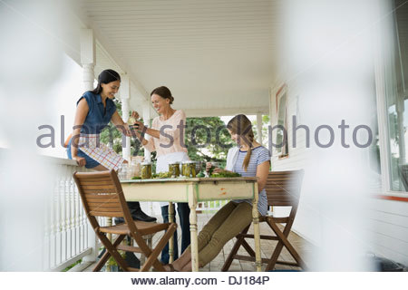 Mother and daughters canning vegetables on porch - Stock Photo