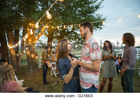 Romantic young couple dancing at outdoor farm party - Stock Photo