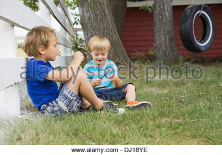 Young boys relaxing in back yard - Stock Photo