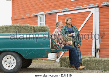 Smiling father and son having coffee by pick-up truck - Stock Photo
