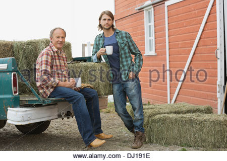 Father and son having coffee by pick-up truck with hay bales - Stock Photo