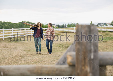Father and son fixing fence planks on farm - Stock Photo
