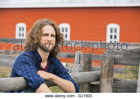 Portrait of happy man leaning against fence - Stock Photo