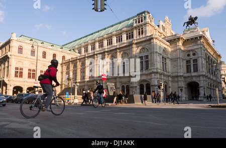 Vienna Opera House and Bicyclist. A cyclist crosses the street in front of the massive Vienna State Opera House. - Stock Photo