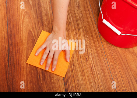 Woman's hand cleaning the floor with yellow sponge - Stock Photo