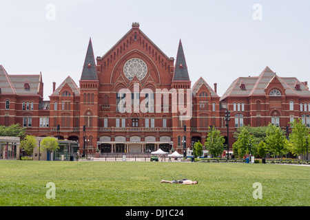 Cincinnati Music Hall with Sunbather. A young man catches a few spring rays on the lawn in front of the red brick - Stock Photo