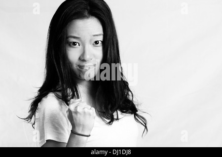 Portrait of attractive young woman clenching her fist for encouragement, black and white style - Stock Photo