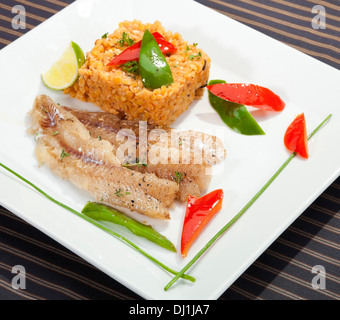 Grilled codfish with red lentil and bell pepper slices - Stock Photo