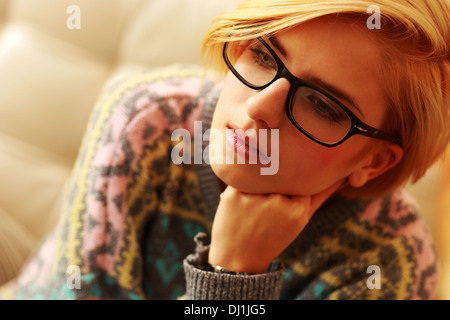Closeup portrait of a young thoughtful woman in glasses - Stock Photo