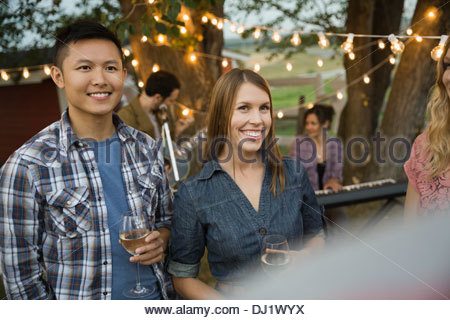 Group of friends enjoying outdoor party with band playing - Stock Photo