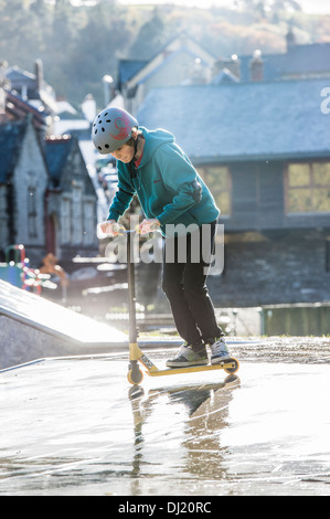 A Teenage boy wearing helmet riding his scooter at a skateboard/BMX park UK - Stock Photo