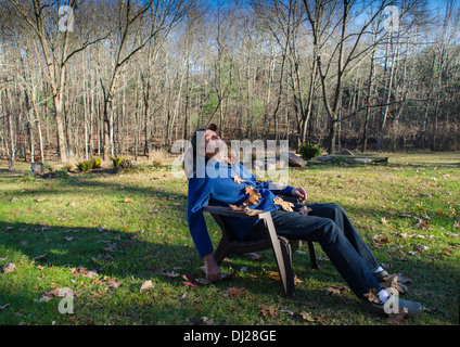 man smiling on lawn chair covered with leaves - Stock Photo