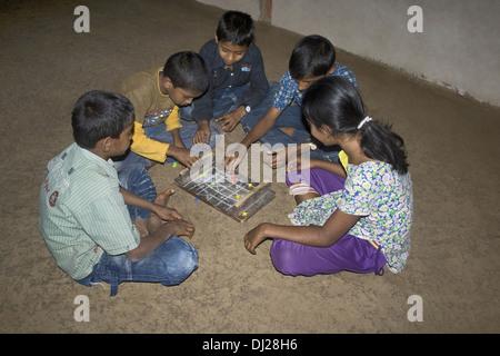 Children playing indoor game Pat (Ludo), Pabal, Pune, Maharashtra, India - Stock Photo