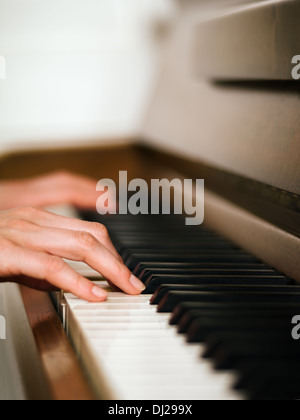 Photo of female hands playing an upright piano. Very shallow depth of field with focus on fingers. - Stock Photo