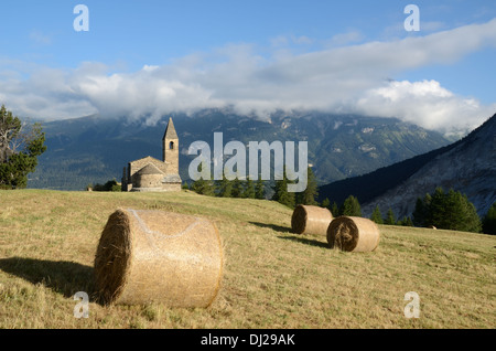 Hay Bales in front of Eglise St-Pierre Extravache & Vanoise National Park Bramans Haute Maurienne Savoie France - Stock Photo