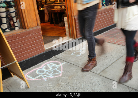 Pedestrians on Biltmore Avenue walk past a chalk drawing promoting local art, Asheville, North Carolina, USA - Stock Photo