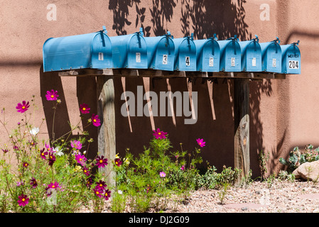 A row of turquoise mailboxes stands in front of an adobe wall on Garcia St. in Santa Fe, New Mexico. - Stock Photo
