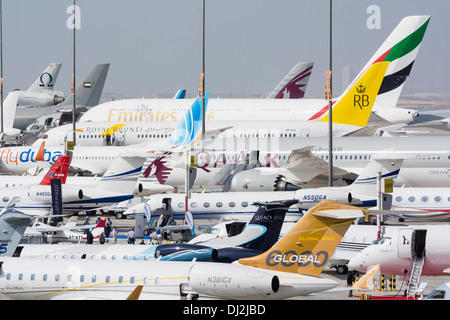 Many aircraft on apron at Al Maktoum International airport during Dubai Airshow 2013 in United Arab Emirates - Stock Photo