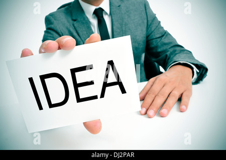 man wearing a suit sitting in a table showing a signboard with the word idea written in it - Stock Photo
