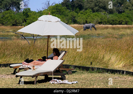 A tourist rests peacefully sunbathing at Camp Khwai River Lodge by Orient Express in Botswana, within the Moremi - Stock Photo