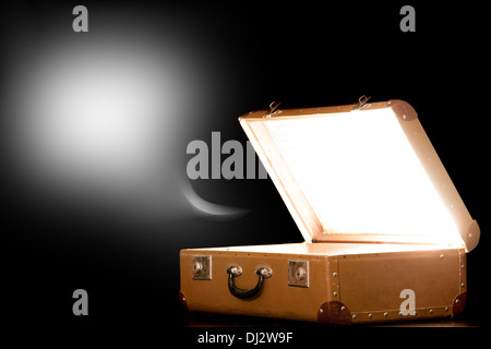 Open suitcase on black background - Stock Photo