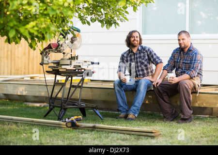 Carpenters Holding Disposable Cups While Sitting On Wooden Frame - Stock Photo