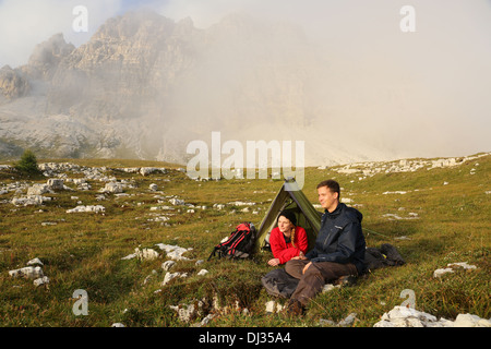 Young people camping in the mountains in fog and enjoying the sunset - Stock Photo