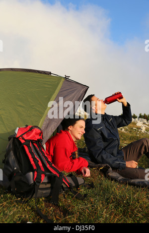 Young couple with a tent is watching the sunset in the mountains - Stock Photo