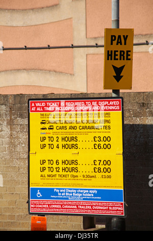 Pay Here car park sign with details of parking charges at Weymouth - Stock Photo