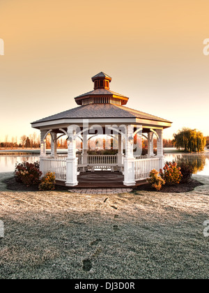 gazebo with footprints on frost covered grass - Stock Photo