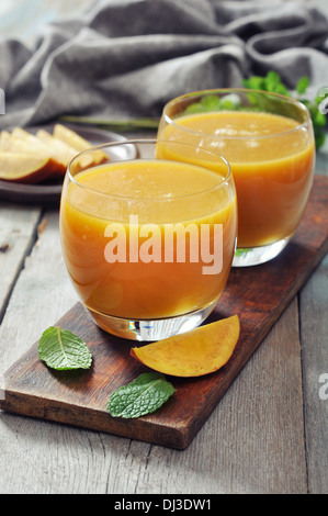 Mango smoothie in glass with mint on wooden background - Stock Photo