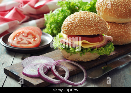 Sandwich with ham, cheese, tomato and lettuce on wooden cutting board closeup - Stock Photo