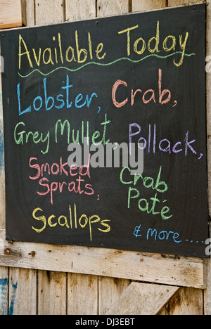 Blackboard on a timber door advertising fish for sale. - Stock Photo