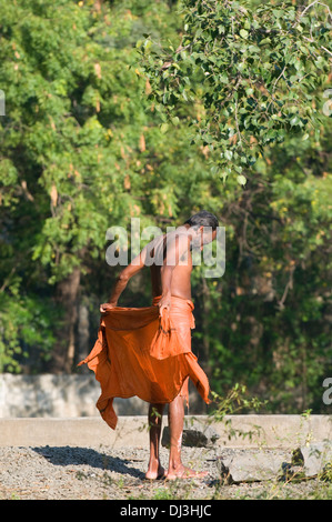 Sadhu, Indian holy man, drying himself and his dhothi and shirt after bathing in the local washing tank in Tiruvannamalai - Stock Photo