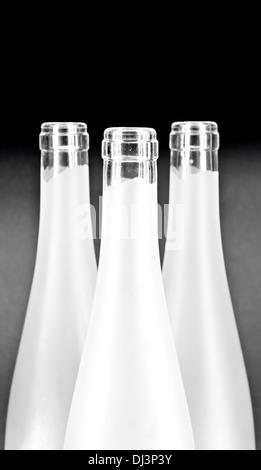White wine bottles bottle necks on dark background - Stock Photo